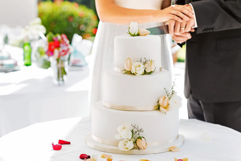 Newlywed Couple Cutting Cake During Reception
